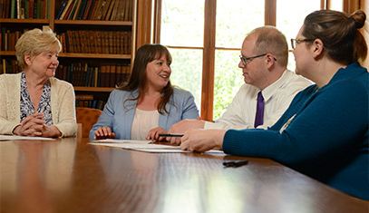 Four staff discussing in a conference room