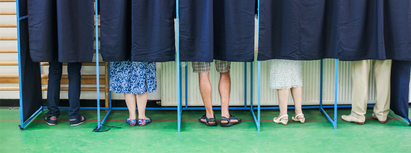 Multiple pairs 的 legs behind curtains at voting booths